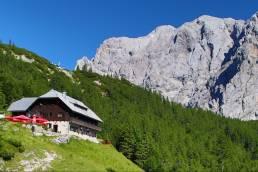 Das Vrsic Pass Panorama in Slowenien mit Bergen, Wäldern und einem Haus