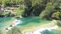 Ein Wasserfall, Wald und Häuser im Krka Nationalpark Kroatien