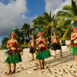 Einheimische tanzen in typischer Kleidung am Strand von Rarotonga, Cookinseln