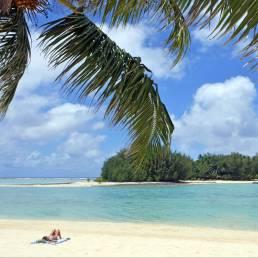 Der Strand und eine Insel im Meer vor Rarotonga, Cookinseln