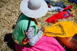 Eine Frau des Uru-Volkes im Titicacasee in Peru webt mit bunten Stoffen