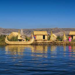 Schwimmende Inseln und ein Schilfboot im Titicacasee in Peru