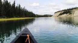Eine Kanuspitze ragt in das Panorama des Yukon Rivers in Kanada