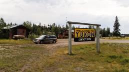 Ein Yukon Territory Schild und ein Fahrzeug an der Grenze zum Yukon in Kanada