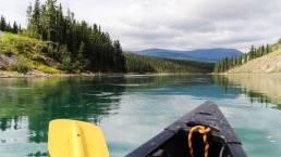 Ein Kanu und Paddel auf dem Yukon River in Kanada, im Hintergrund die Wälder