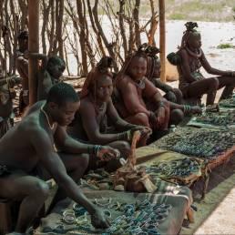 Ein Mann des Himba-Stammes, seine Frauen und Kinder zeigen ihren Schmuck