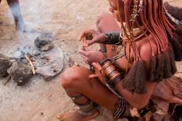 Eine Himba-Frau sitzt an einer Feuerstelle in Namibia