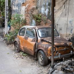 Ein kaputtes und rostendes Auto steht am Straßenrand in Bangkoks Stadtviertel Talad Noi in Thailand als Schrott