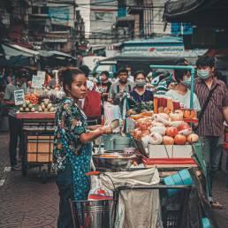 Eine Frau verkauft auf einem Street Food Markt in Bangkok Thailand ihre Produkte