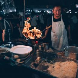Bei den HiveSters auf einem Street Food Markt in Thailand können die Besucher das Essen selber im Wok zubereiten