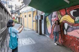 Frau lässt sich vor Graffiti in Bongkoks Stadtviertel Talad Noi fotografieren