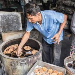 Ein Mann in Bangkoks Stadtviertel Talad Noi bereitet Kanom Farang Kudeejeen zu