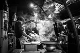 Ein Street Food Stand auf einem Markt in Bangkok Thailand in welchem mit einem Wok gekocht wird