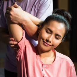 Frau wird der Arm nach hinten gebogen bei einer Thai Massage in Thailand