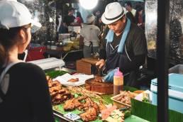 Nacht Markt in Phuket Thailand wo ein Mann frisch Essen zubereitet