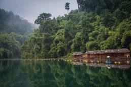 Ein Fluss in Thailand mit Bergen und Nebel während der Regensaison in Thailand